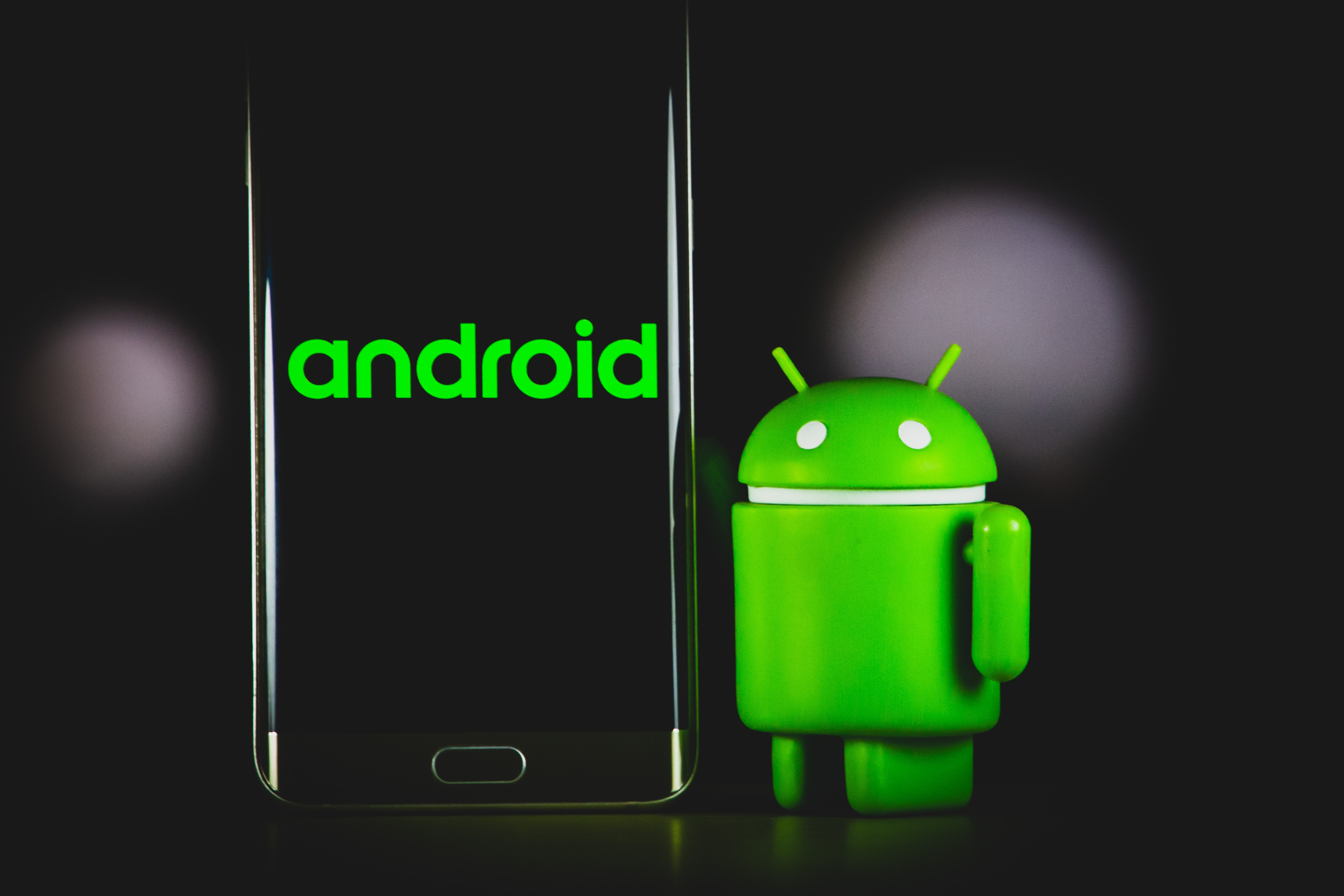 Image of the Android logo beside a smartphone against a black background.