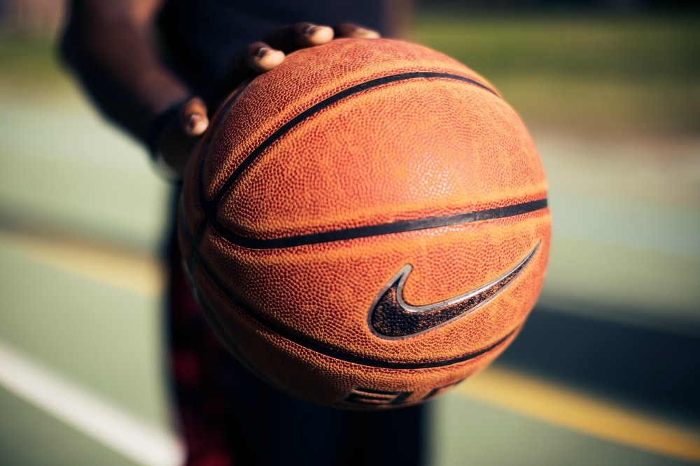 Basketball player holding an orange basketball with a Nike swoosh logo in one hand