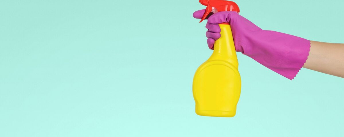 Hand in rubber glove holding a spray bottle of bleach