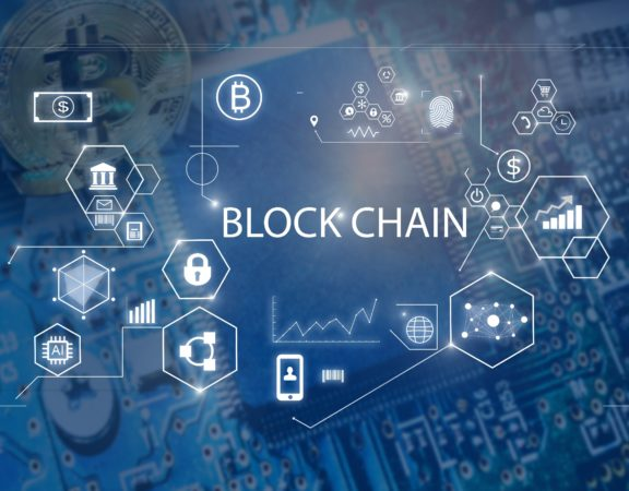 The word blockchain surrounded by symbols of bitcoin, finances, mobile devices, money, computer networks.