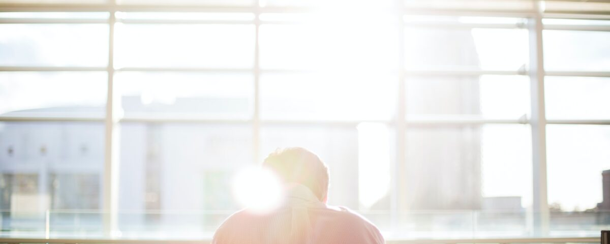 Business person sitting a board room table in front of sunny window