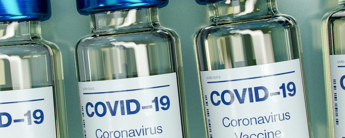 Photograph of a row of glass bottles containing vaccines against COVID-19.