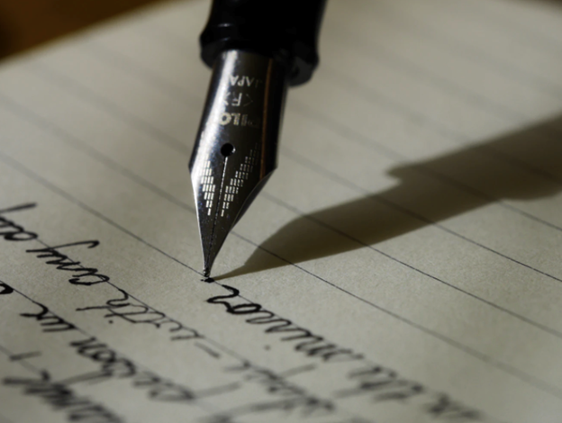 Close-up photograph of a fountain pen writing words in ink on paper.