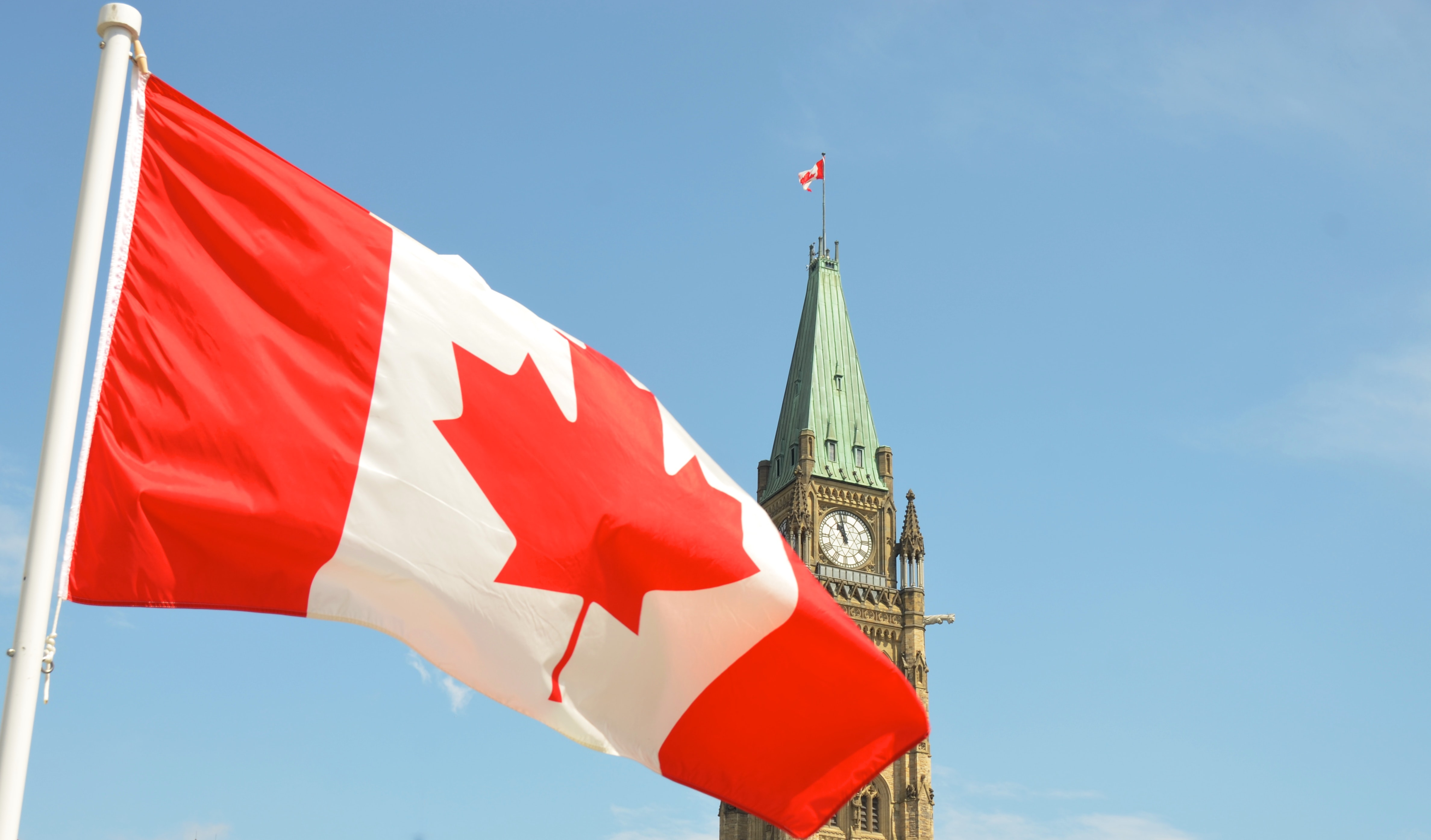 Canadian flag waving in front of the Parliament buildings in Ottawa.