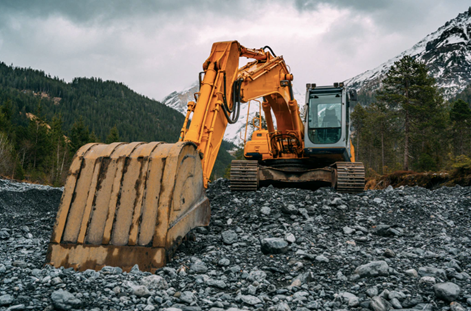 An orange backhoe on a construction site with mountains in the background.