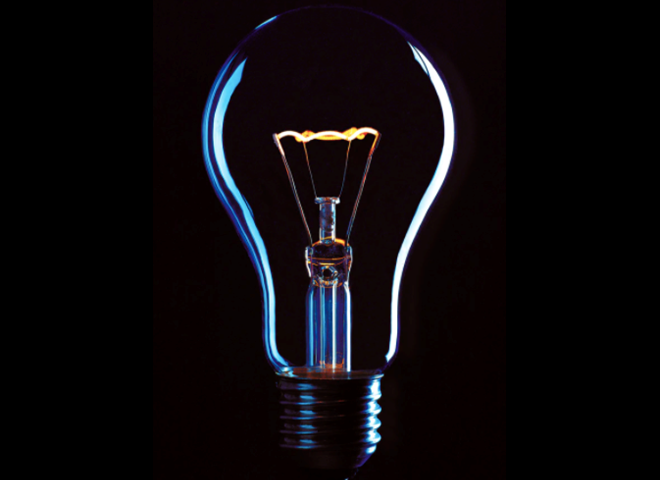 Electricity powering a lightbulb on a black background.