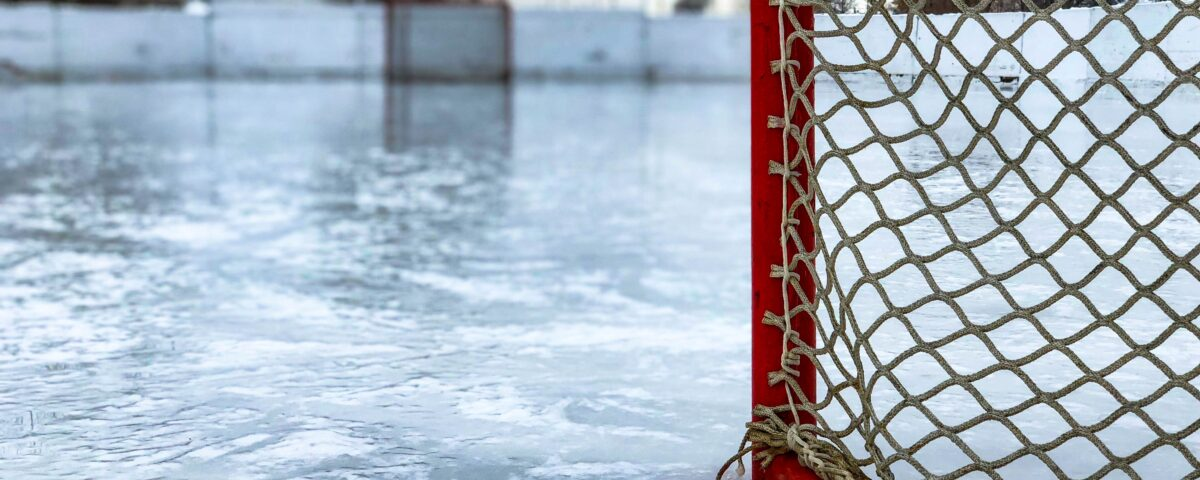 Photograph of a red hockey net on the ice of an outdoor skating rink.