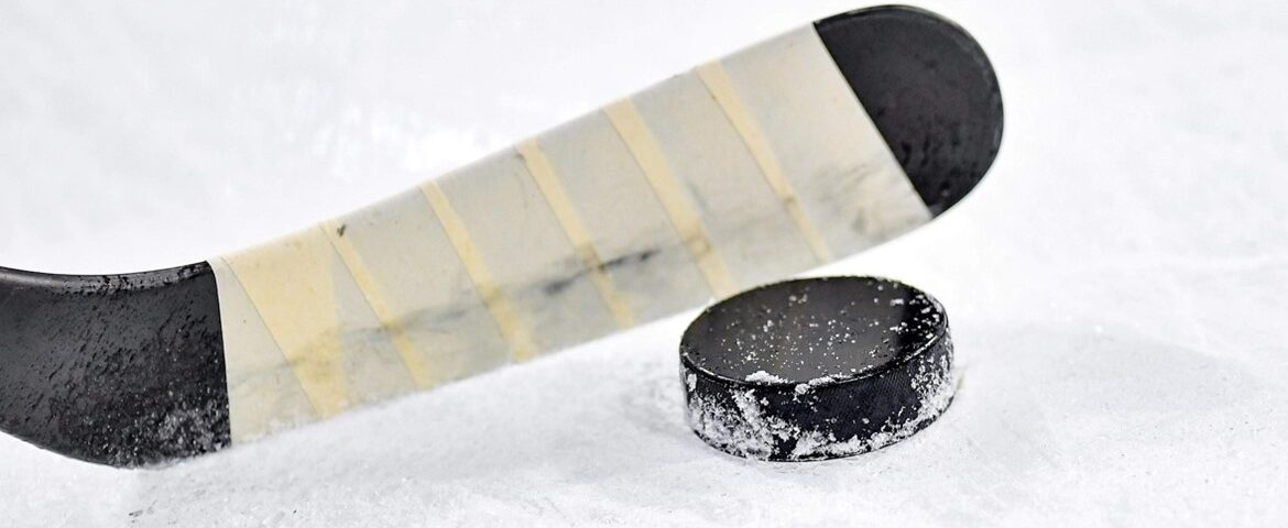 photo of a hockey stick and a hockey puck on an ice rink.