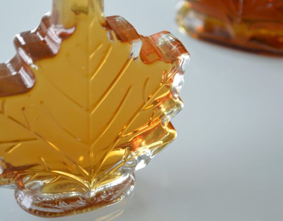 Photo of a glass, maple-leaf-shaped bottle containing maple syrup.
