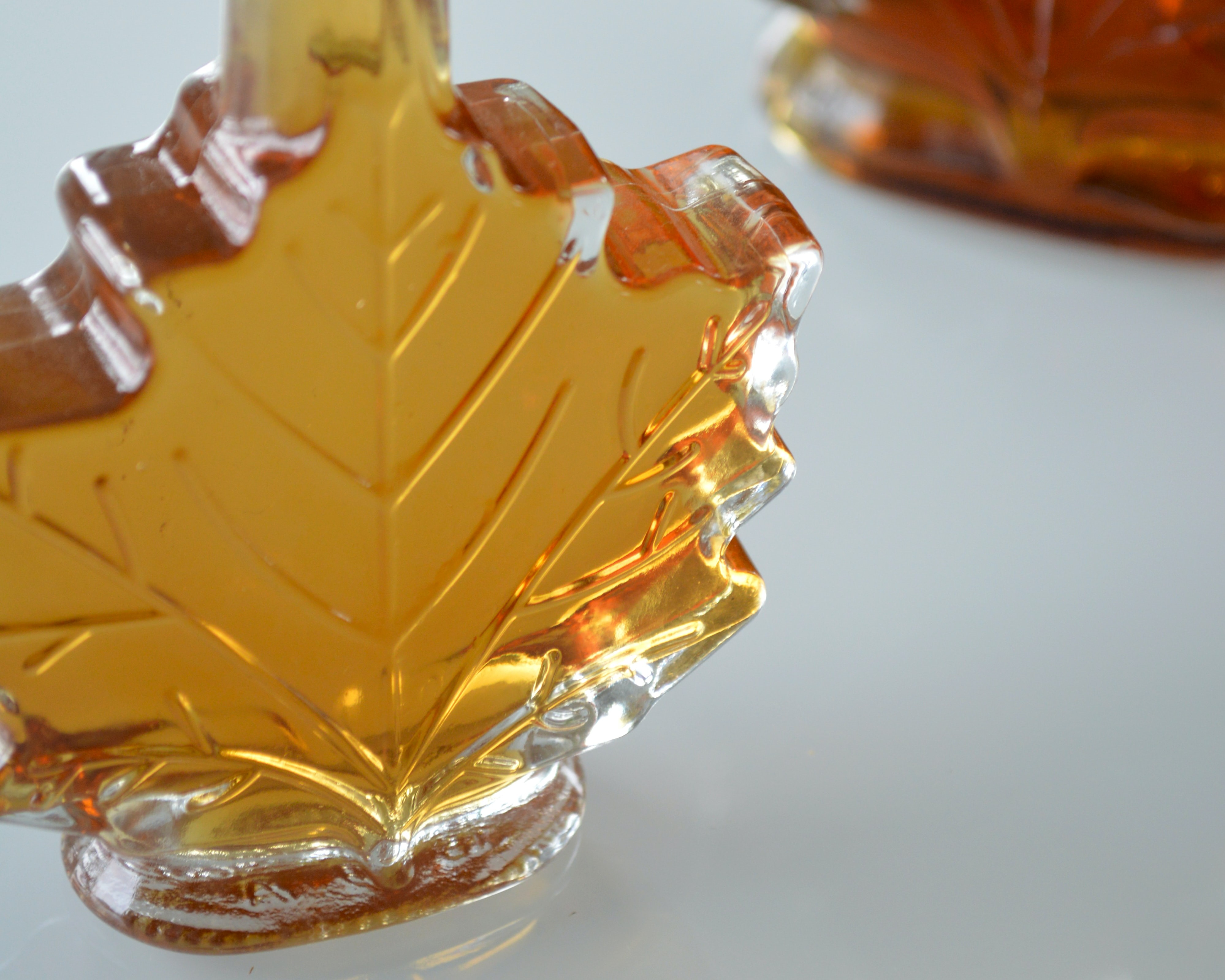 Photo of a glass maple leaf shaped bottle containing maple syrup.
