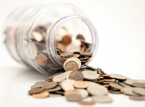 Photograph of a money jar spilling coins against white background.