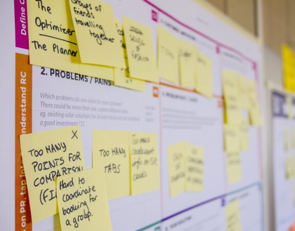 Photo of a project planning board covered in yellow sticky notes.