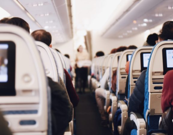 Photo of the interior of an airplane cabin, showing a row of seats.