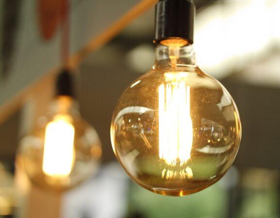 Lightbulbs in a row. Lightbulbs are illuminated, Edison-style glass bulbs.