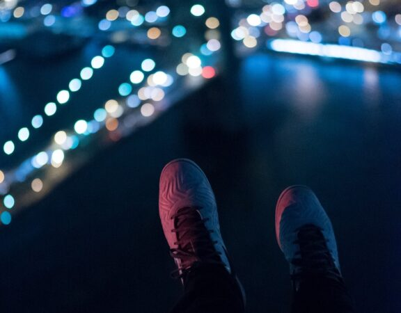 Photo of a pair of shoes dangling off the edge of a building while lights shine on a bridge in the distance at night.