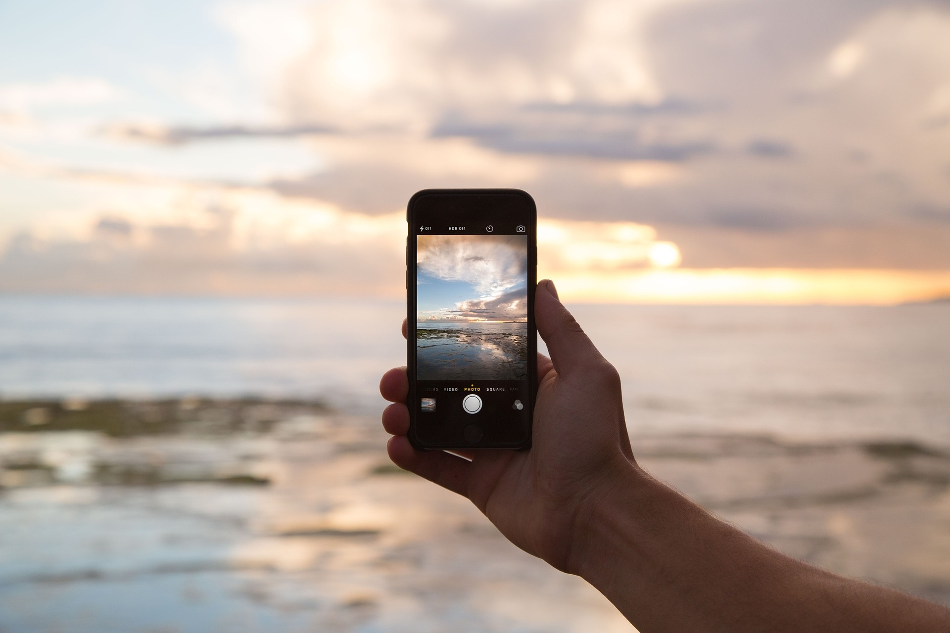 Photograph of a smartphone taking a photo of a sunset on a beach.