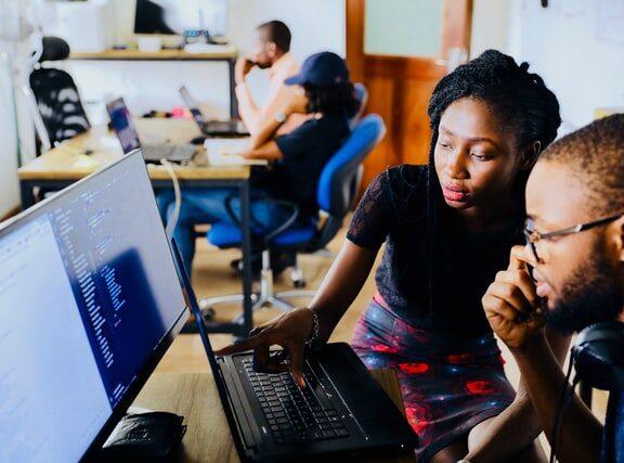 A mentor teaching an intern about computer software
