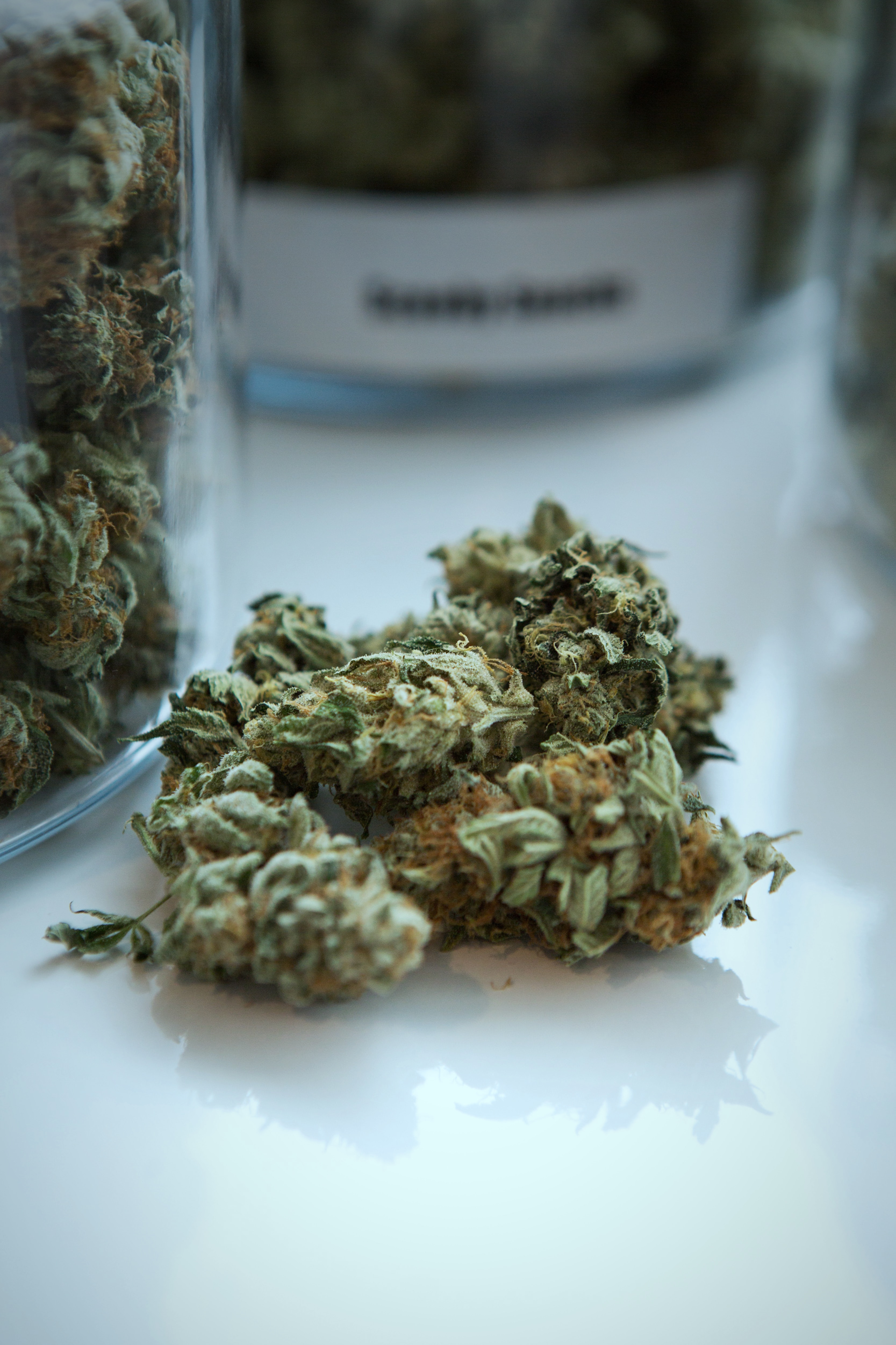 A photo of cannabis buds on a white counter beside jars of product for sale.