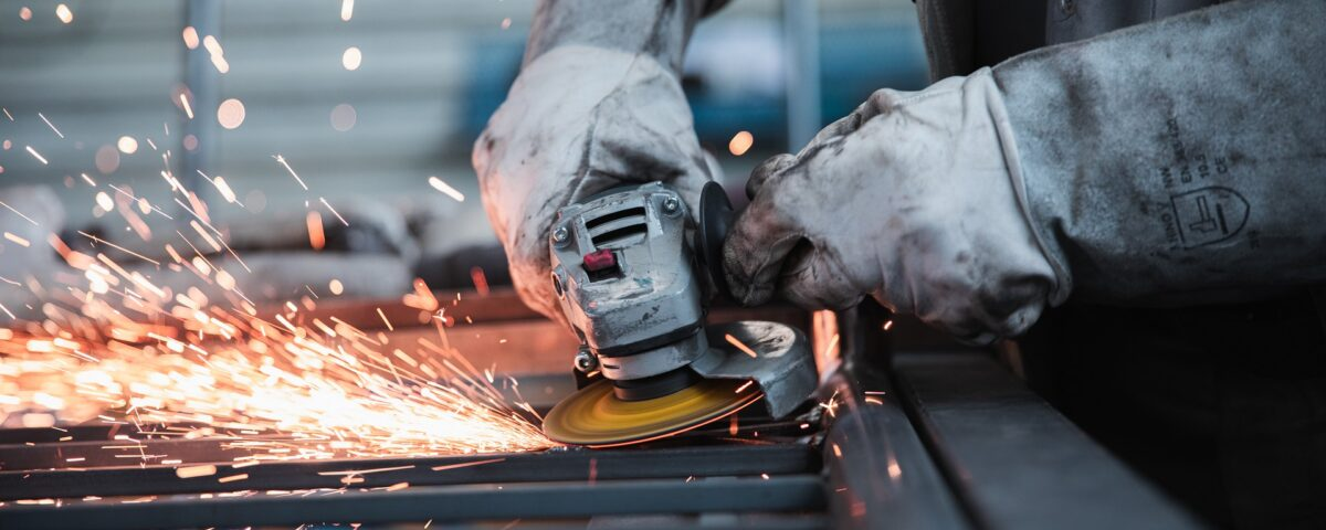 A metal worker using an angle grinder to cut steel.